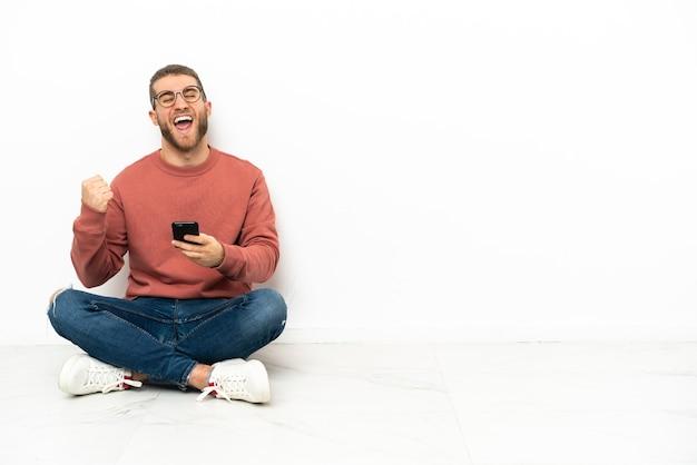 Młody przystojny mężczyzna siedzący na podłodze z telefonem w pozycji zwycięstwa