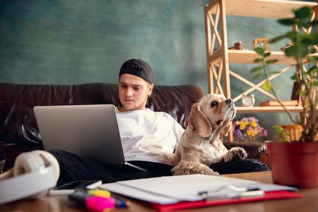 Młody przystojny mężczyzna siedzi na brązowej kanapie i pracuje ze swoim uroczym psem