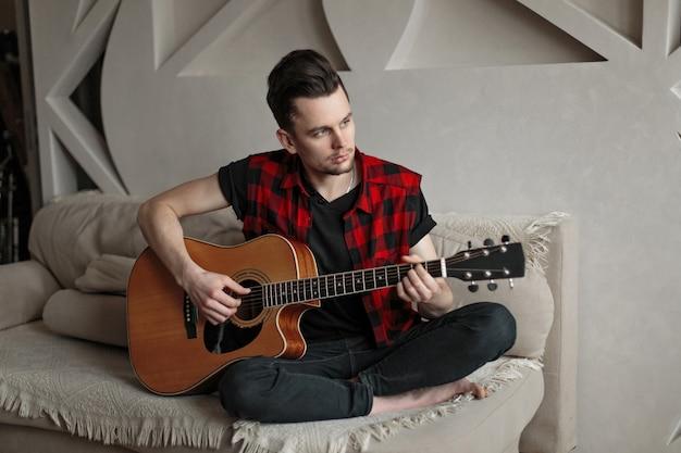 Młody przystojny mężczyzna siedzi na kanapie i gra na gitarze