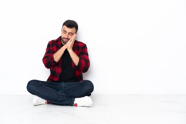 Młody przystojny mężczyzna siedzi na podłodze, czyniąc gest snu w dorable wypowiedzi