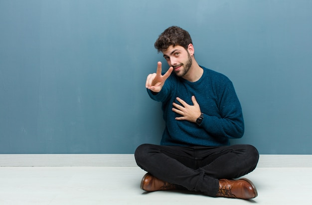Młody przystojny mężczyzna siedzi na podłodze patrząc szczęśliwy, pewny siebie i godny zaufania, uśmiechnięty i pokazując znak zwycięstwa, z pozytywnym nastawieniem