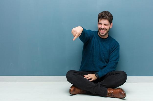Młody przystojny mężczyzna siedzi na podłodze, śmiejąc się z ciebie, wskazując na aparat i wyśmiewając się z ciebie