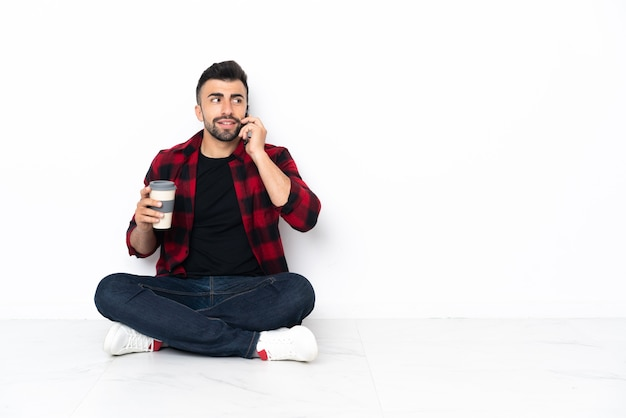 Młody przystojny mężczyzna siedzi na podłodze trzymając kawę na wynos i telefon komórkowy