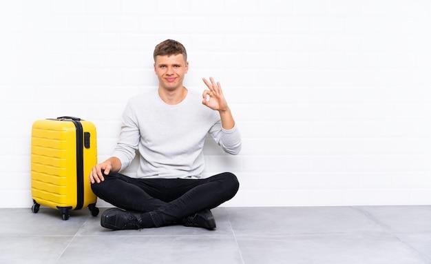 Młody przystojny mężczyzna siedzi na podłodze z walizką pokazującą znak ok palcami