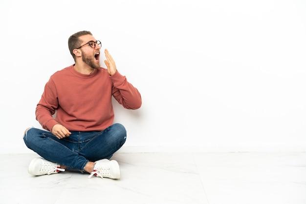 Młody przystojny mężczyzna siedzi na podłodze, ziewając i obejmując ręką szeroko otwarte usta