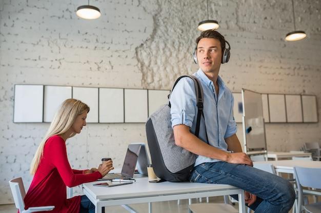 Młody przystojny mężczyzna siedzi na stole w słuchawkach z plecakiem w biurze współpracującym pije kawę