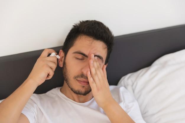 Młody przystojny mężczyzna siedzi na swoim łóżku. trzyma spray z lekarstwami, musi wyleczyć ucho.