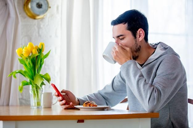 Młody przystojny mężczyzna siedzi przy stole z filiżanką kawy lub herbaty i telefonu komórkowego. lokalizacja kuchni rano