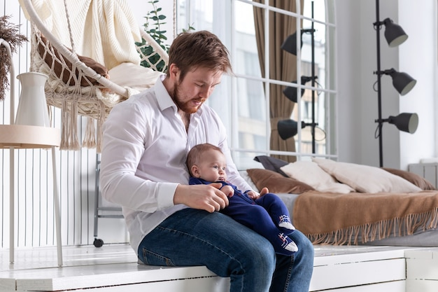 Młody przystojny mężczyzna siedzi w nowoczesnym wnętrzu sypialni z małym synkiem na kolanach