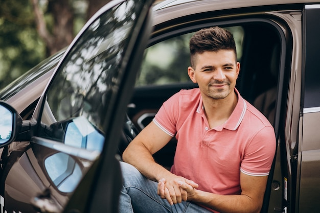 Młody przystojny mężczyzna siedzi w samochodzie