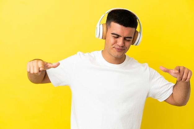 Młody przystojny mężczyzna słucha muzyki i tańca na odosobnionym żółtym tle