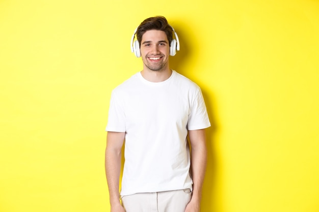 Młody przystojny mężczyzna słucha muzyki w słuchawkach, nosi słuchawki i uśmiecha się, stojąc na żółtym tle.