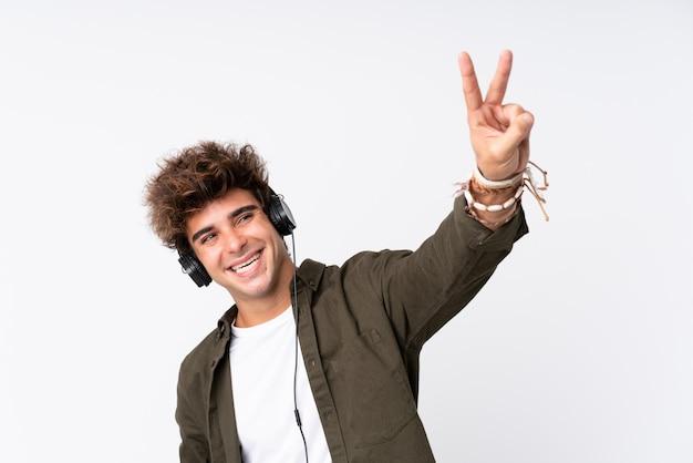 Młody przystojny mężczyzna słuchania muzyki na białej ścianie