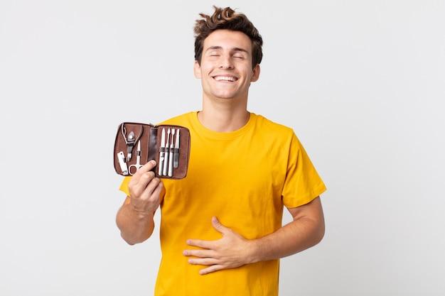 Młody przystojny mężczyzna śmiejący się głośno z jakiegoś przezabawnego żartu i trzymający walizkę z narzędziami do paznokci