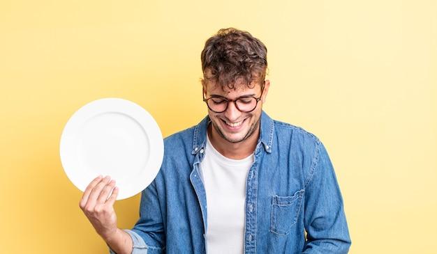 Młody przystojny mężczyzna śmiejący się głośno z jakiegoś przezabawnego żartu. koncepcja pustego naczynia