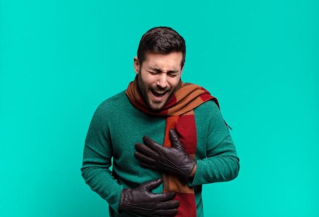 Młody przystojny mężczyzna śmiejący się głośno z jakiegoś przezabawnego żartu, szczęśliwy i wesoły, dobrze się bawiący. zimno i zima koncept