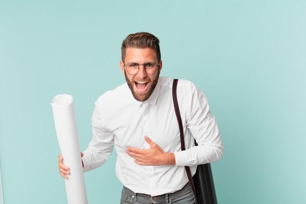 Młody przystojny mężczyzna śmiejący się głośno z jakiegoś zabawnego żartu. koncepcja architekta
