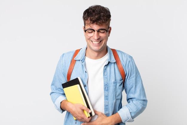 Młody przystojny mężczyzna śmiejący się głośno z jakiegoś zabawnego żartu. koncepcja studenta uniwersytetu