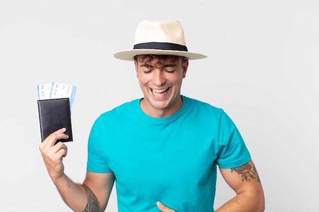 Młody przystojny mężczyzna śmiejący się głośno z jakiegoś zabawnego żartu. podróżnik trzymający paszport