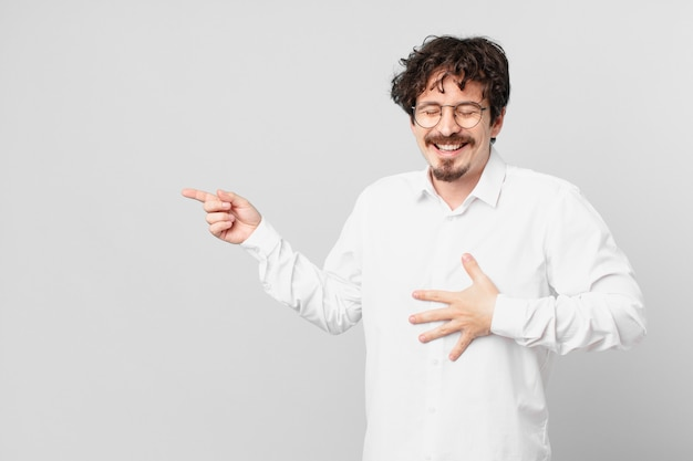 Młody przystojny mężczyzna śmiejący się głośno z jakiegoś zabawnego żartu