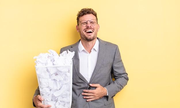Młody przystojny mężczyzna śmiejący się głośno z jakiejś przezabawnej koncepcji papierowych kulek na śmieci