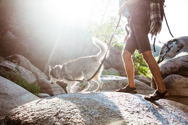 Młody przystojny mężczyzna spaceru z psem husky w kanionie w pobliżu wody
