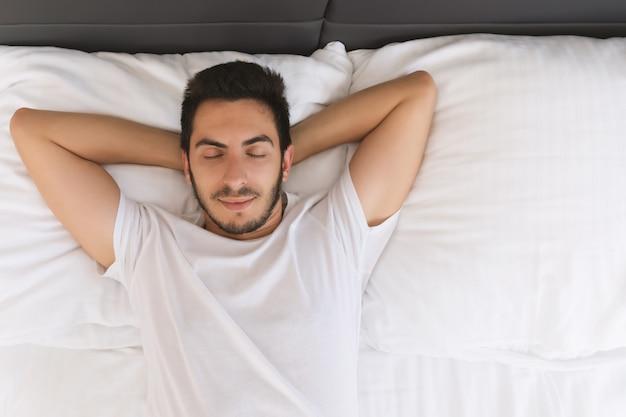 Młody przystojny mężczyzna śpi w swoim łóżku.