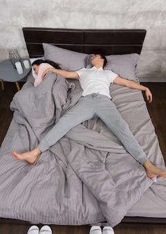 Młody przystojny mężczyzna śpiący w pozycji swobodnego spadania ze swoją dziewczyną zajął całe łóżko, ubrany w piżamę, przy stoliku nocnym ze świecami