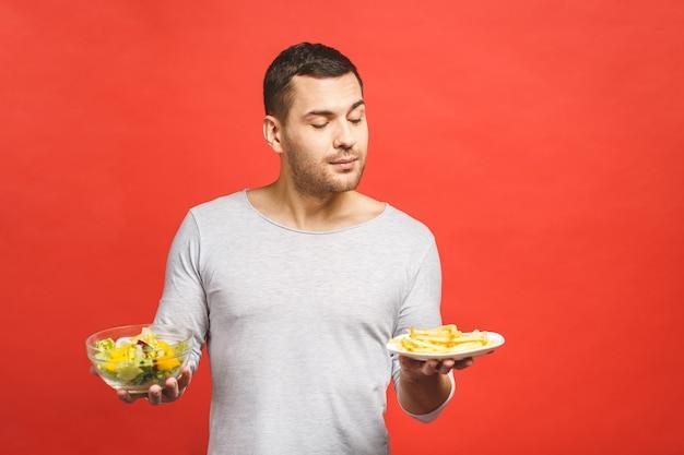 Młody przystojny mężczyzna spragniony fast foodów zamiast zdrowego jedzenia
