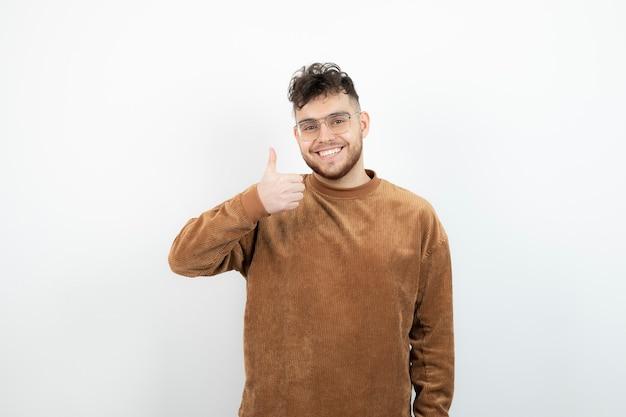 Młody przystojny mężczyzna, stojąc i dając kciuki do góry.