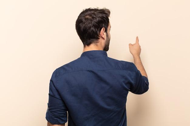 Młody przystojny mężczyzna stojący i wskazujący na obiekt na przestrzeni kopii, widok z tyłu