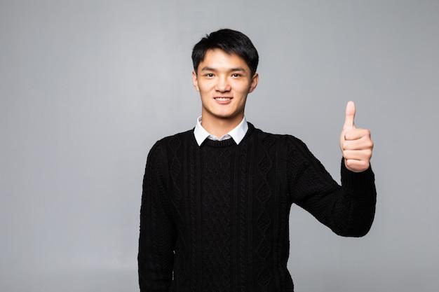 Młody przystojny mężczyzna stojący na sobie na białej ścianie.