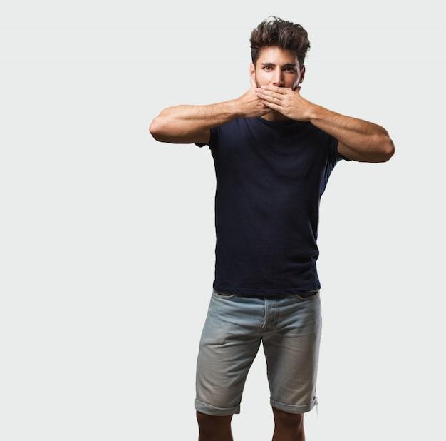 Młody przystojny mężczyzna stojący obejmujące usta, symbol ciszy i represji