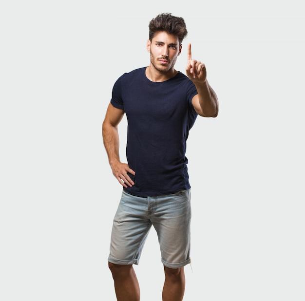 Młody przystojny mężczyzna stojący pokazując numer jeden, symbol liczenia, pojęcie matematyki