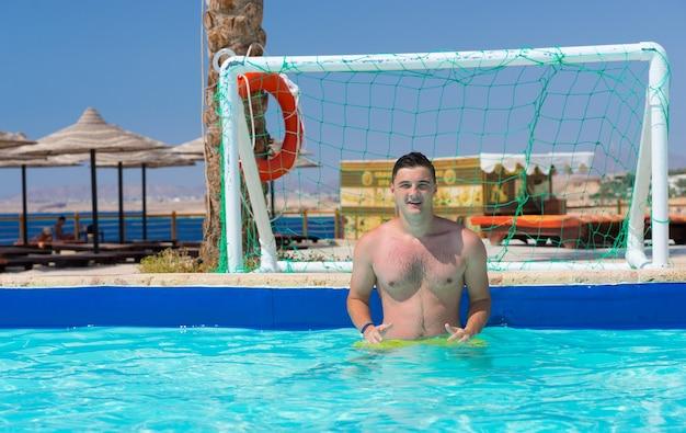 Młody przystojny mężczyzna stojący przy bramie w basenie grając w piłkę wodną w hotelu w słoneczny letni dzień