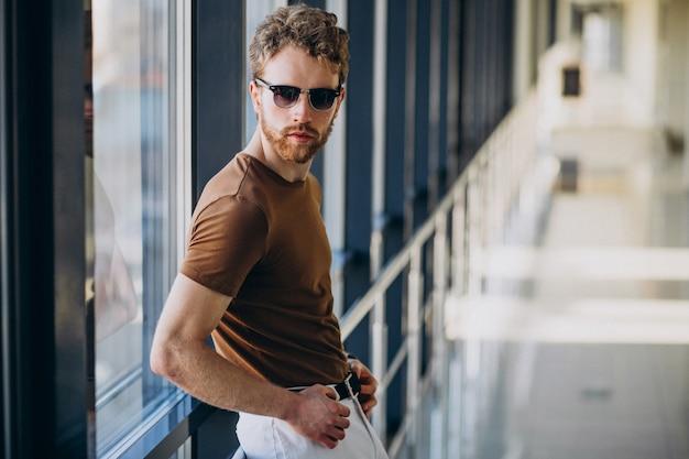 Młody przystojny mężczyzna stojący przy oknie na lotnisku