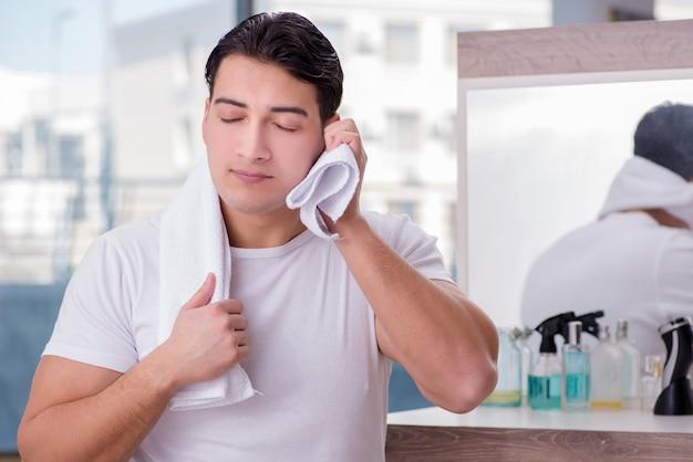 Młody przystojny mężczyzna stosuje krem do twarzy