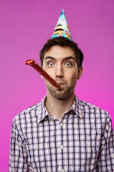 Młody przystojny mężczyzna świętuje przyjęcie urodzinowe nad purpury ścianą.