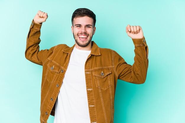 Młody przystojny mężczyzna świętuje wyjątkowy dzień, skacze i energicznie podnosi ramiona.