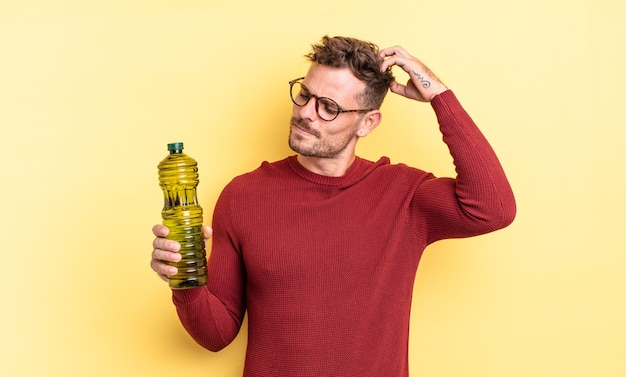 Młody przystojny mężczyzna szczęśliwie uśmiechający się i marzący lub wątpiący. koncepcja oliwy z oliwek