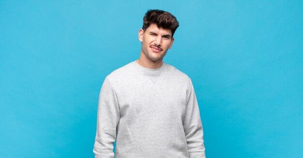 Młody przystojny mężczyzna, szczęśliwy i przyjazny, uśmiechnięty i mrugający okiem z pozytywnym nastawieniem