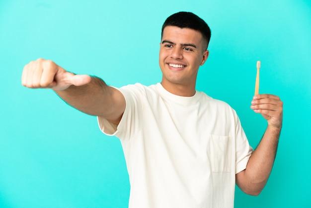 Młody przystojny mężczyzna szczotkuje zęby na odosobnionym niebieskim tle, dając gest kciuka w górę