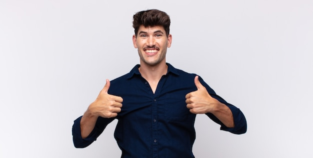 Młody przystojny mężczyzna, szeroko uśmiechnięty, szczęśliwy, pozytywny, pewny siebie i odnoszący sukcesy, z dwoma kciukami do góry