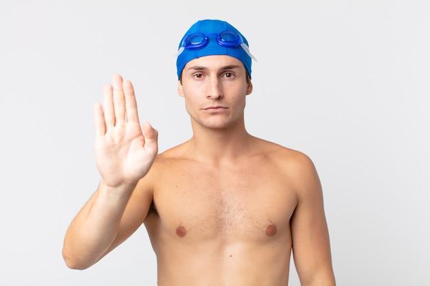 Młody przystojny mężczyzna szuka poważnego wyświetlono otwartej dłoni co gest zatrzymania. koncepcja pływaka