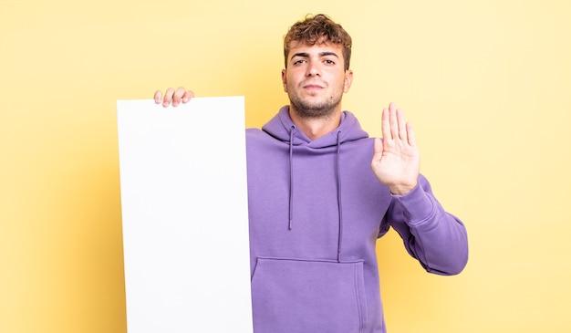 Młody przystojny mężczyzna szuka poważnego wyświetlono otwartej dłoni co gest zatrzymania. kopia koncepcja przestrzeni