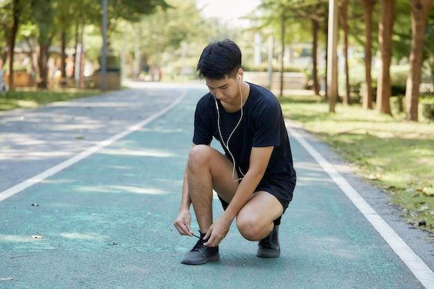 Młody przystojny mężczyzna tajski ćwiczenia na świeżym powietrzu, słuchanie muzyki w parku. skopiuj miejsce na tekst