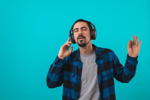 Młody przystojny mężczyzna tańczy i śpiewa piosenki słuchając muzyki w słuchawkach na niebieskim tle