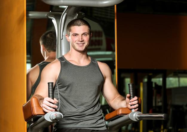Młody przystojny mężczyzna, trening w siłowni