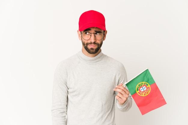 Młody przystojny mężczyzna trzyma flagę portugalii