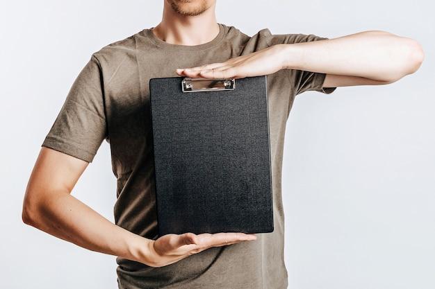Młody przystojny mężczyzna trzyma folder na dokumenty z dokumentami